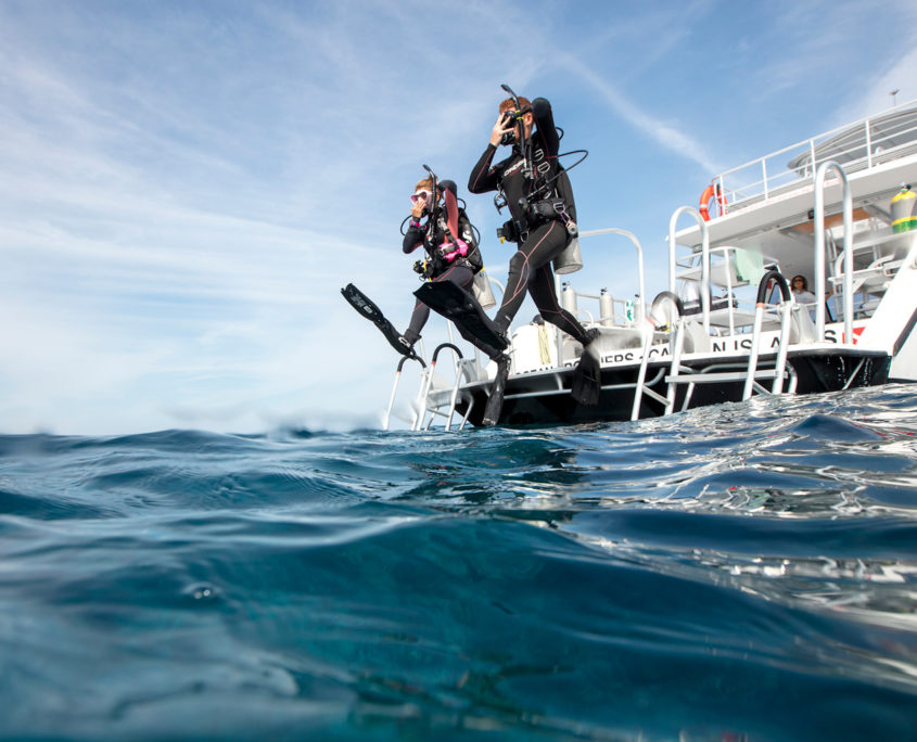 rescue divers jumping from a boat doing the giant step. They wear the full diving equipment and they are holding mask and regulator with one hand.