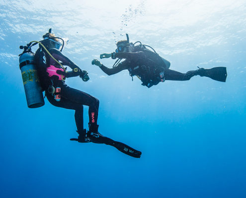 scuba diving instructor teaching diving to a beginner, floating in the sea and mastering floatability