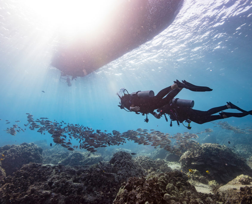 two scuba divers, diving in the sea, under a boat, having a padi-specialities-course,padi-traning-spain, torrox costa