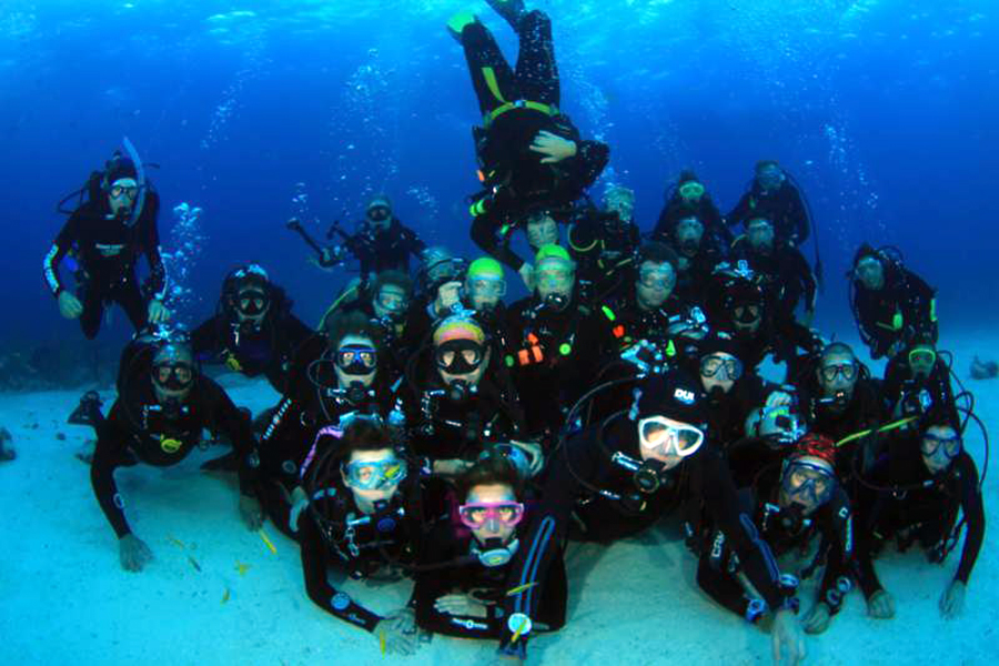 A group of scuba divers posing, on the bottom of the sea, for an underwater picture.